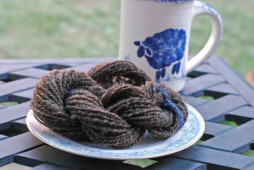 Small twisted skein of handspun combed Shetland wool top on side plate with ceramic sheep mug